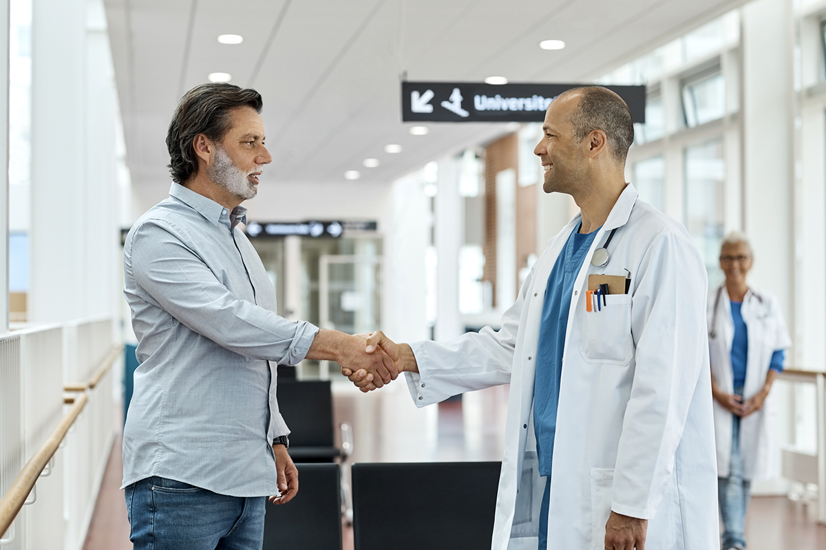 A man shakes hands with a doctor in a hospital hallway