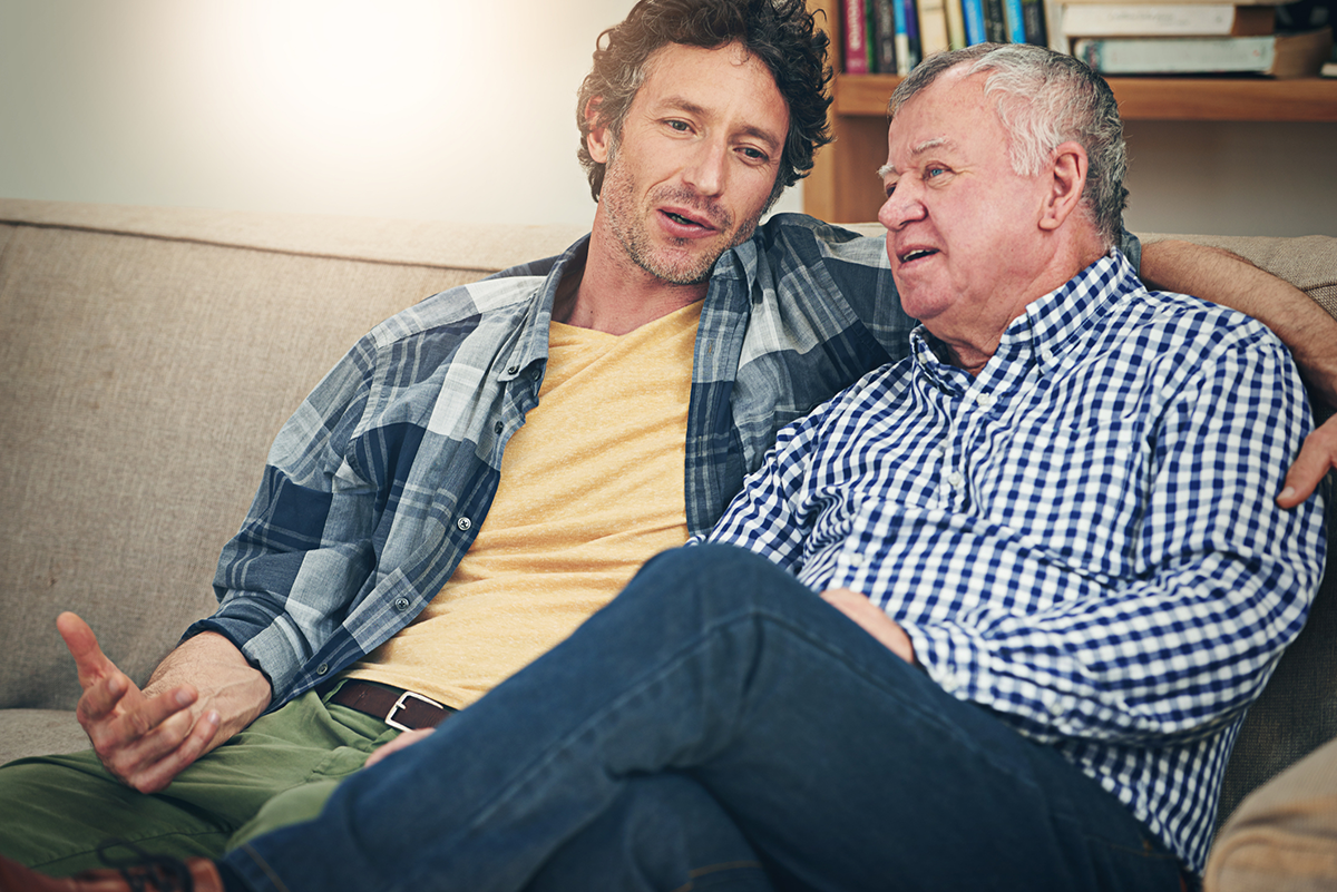 An elderly man listens to a younger man on the couch