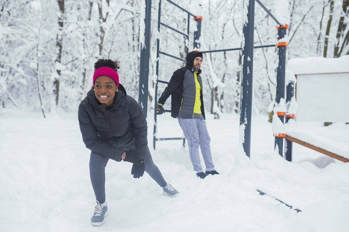 A man and woman stretch before a workout in the snow