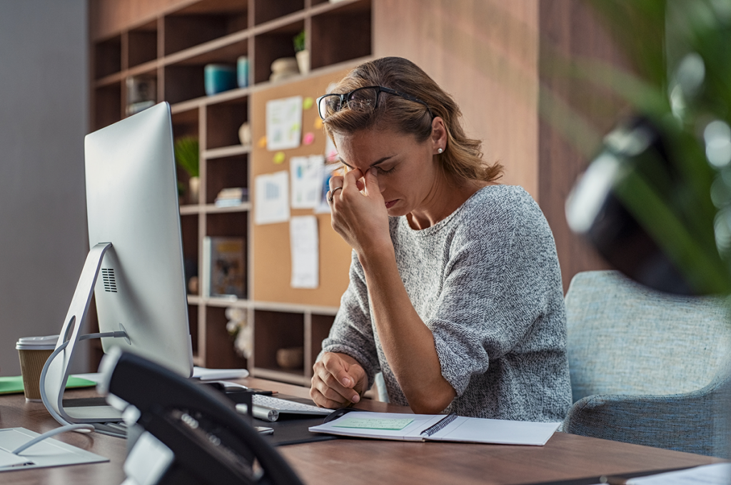 A woman suffering a migraine at her desk.
