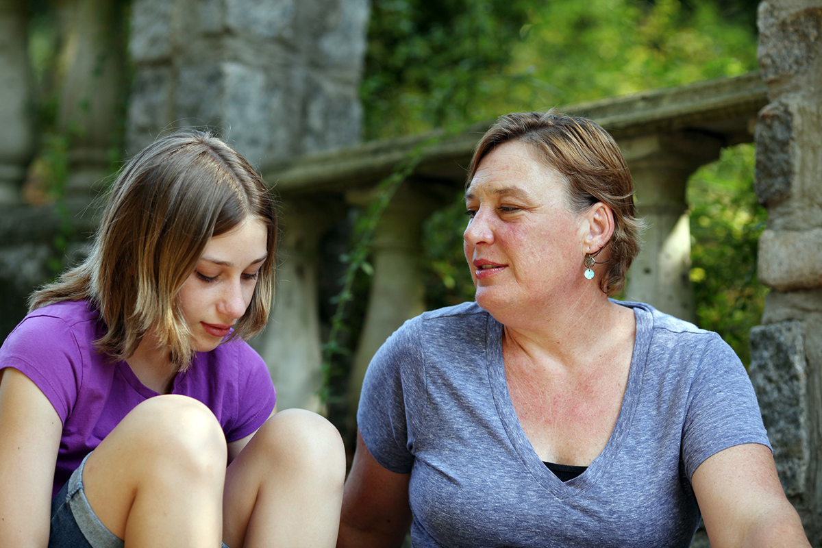 a mother talks with her daughter outdoors