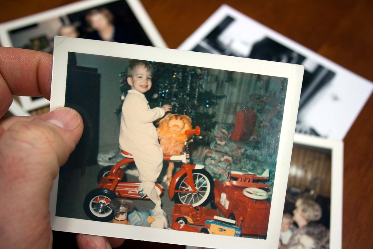 A hand holds a vintage photograph of a boy on a bicycle in front of a Christmas tree.