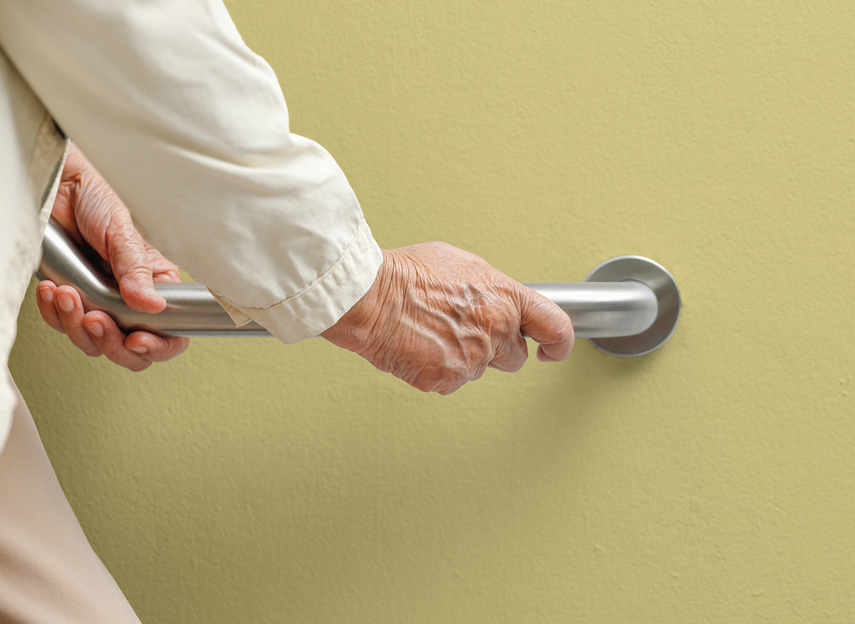 A hand grips a safety handrail