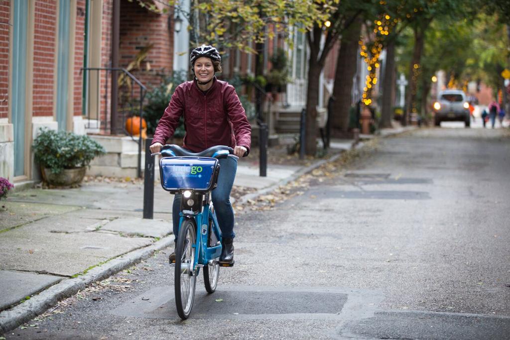 A woman rides an Indego bike down a Philadelphia street