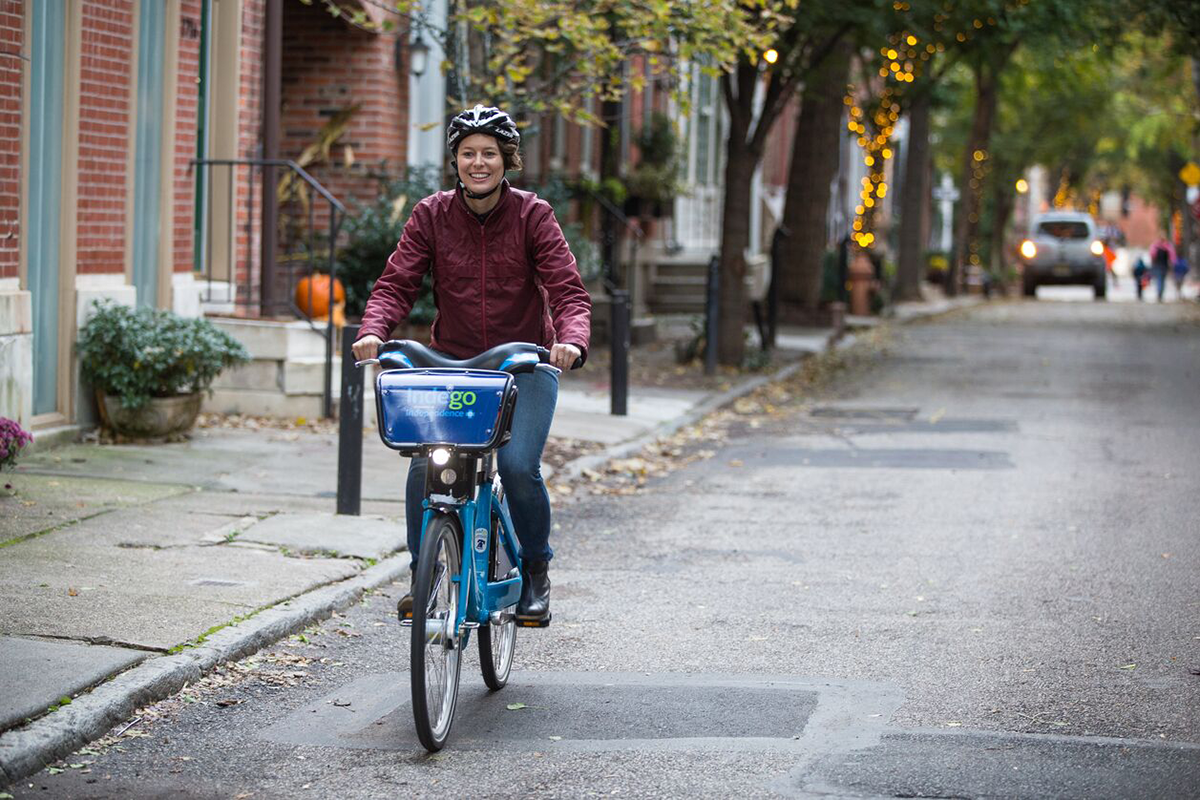 A woman rides an Indego bike down a Philadelphia street