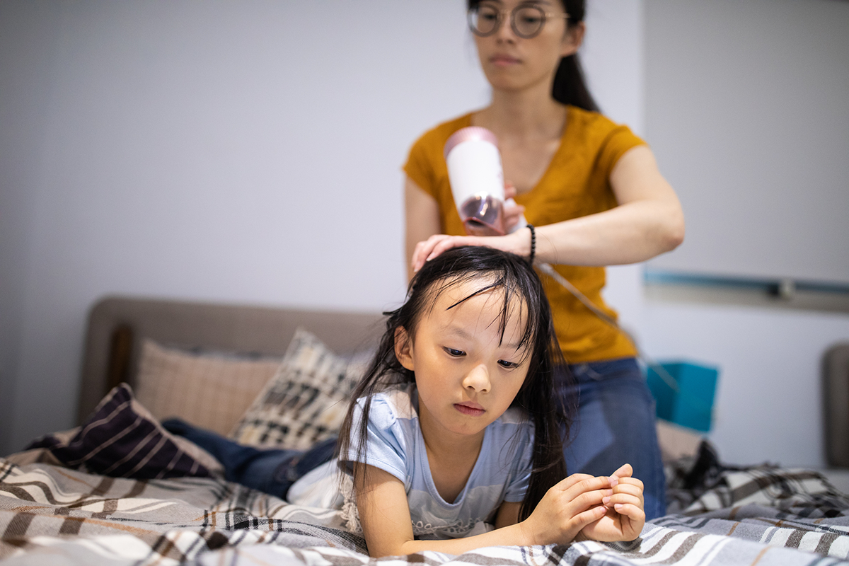A woman dries her young daughter's hair
