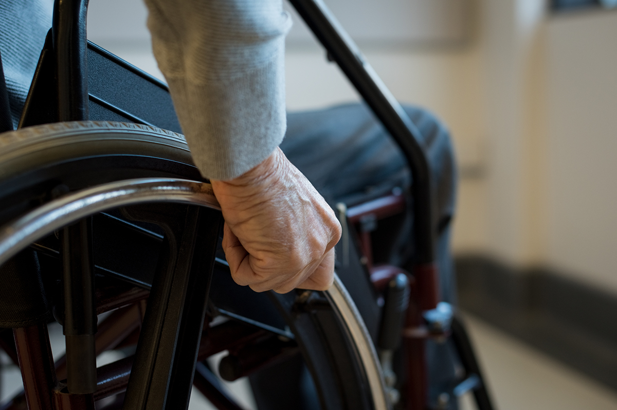 Close-up of a hand gripping the wheel of a wheelchair