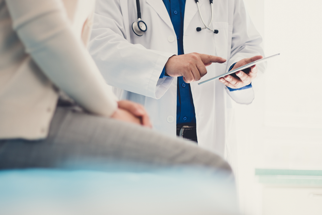 Close-up of a doctor pointing to a tablet, with a patient sitting in the foreground.