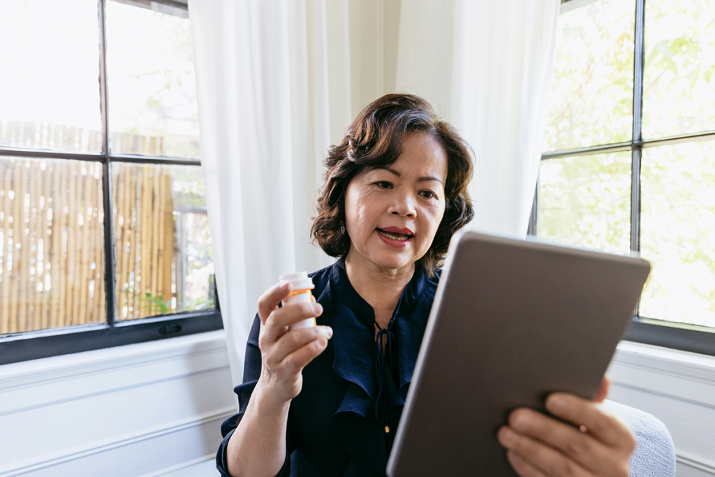 A woman consults with her physician remotely via tablet, whole holding a bottle of pills