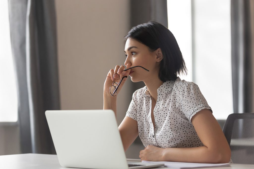 Thoughtful anxious business woman looking away thinking solving problem