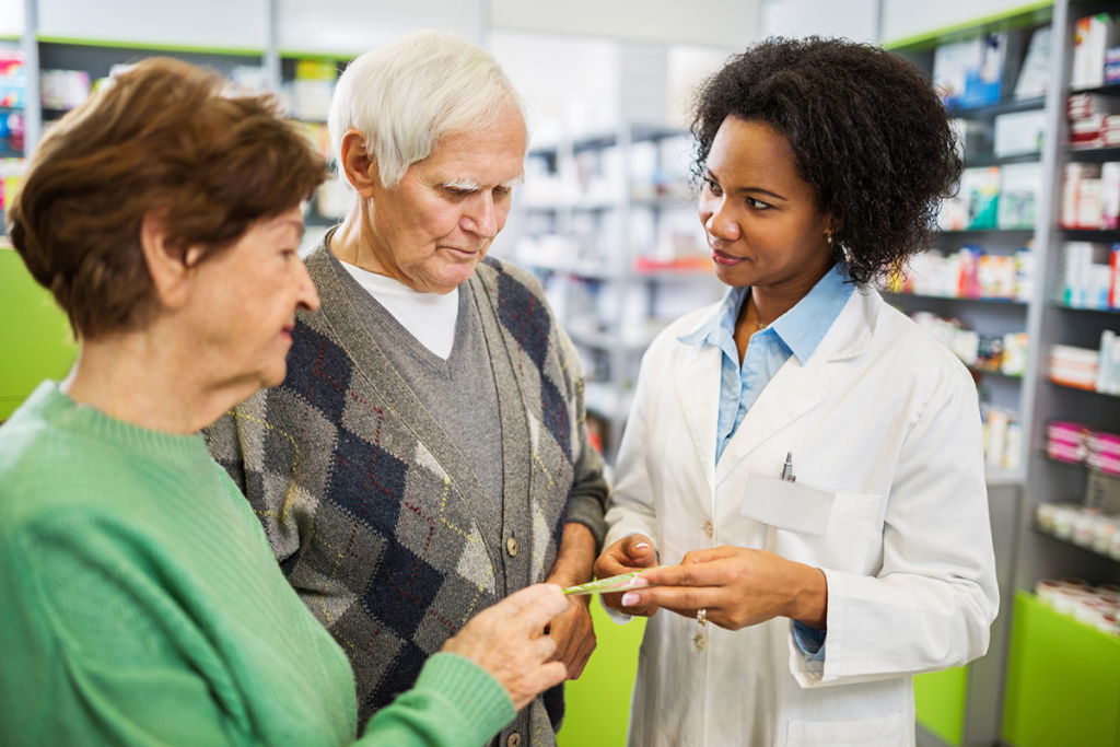 A young pharmacist speaks to two elderly customers