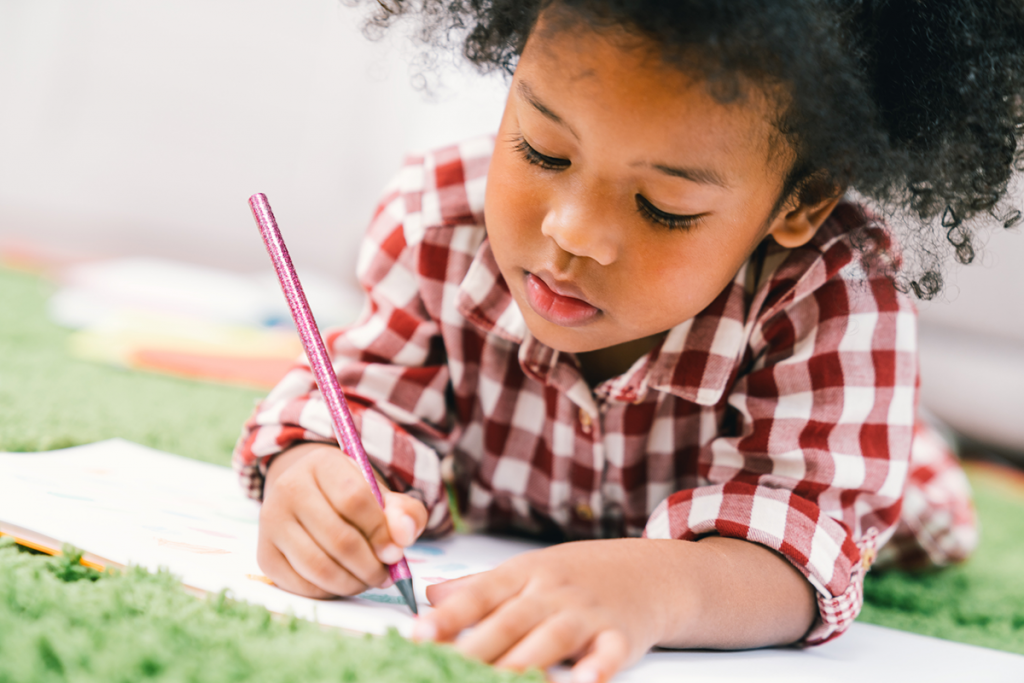 A little girl draws in a coloring book