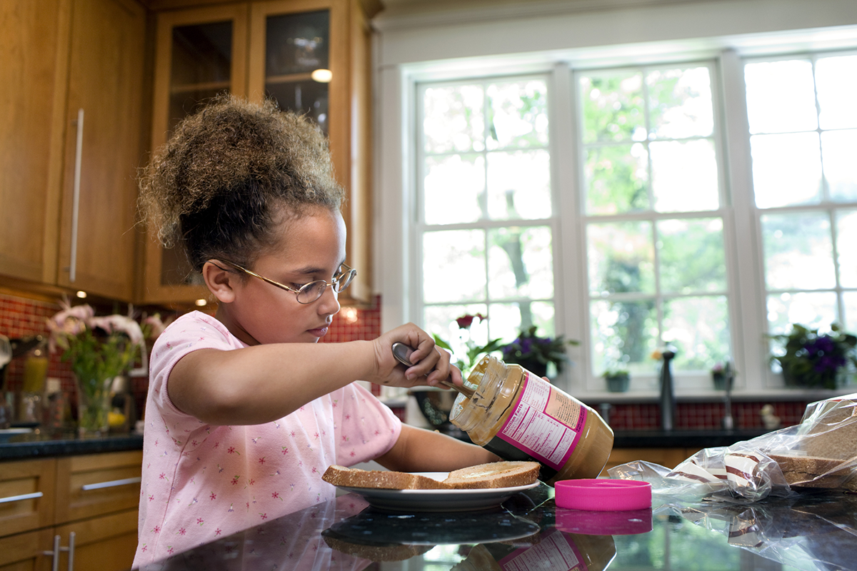A young girl makes a peanut butter sandwich