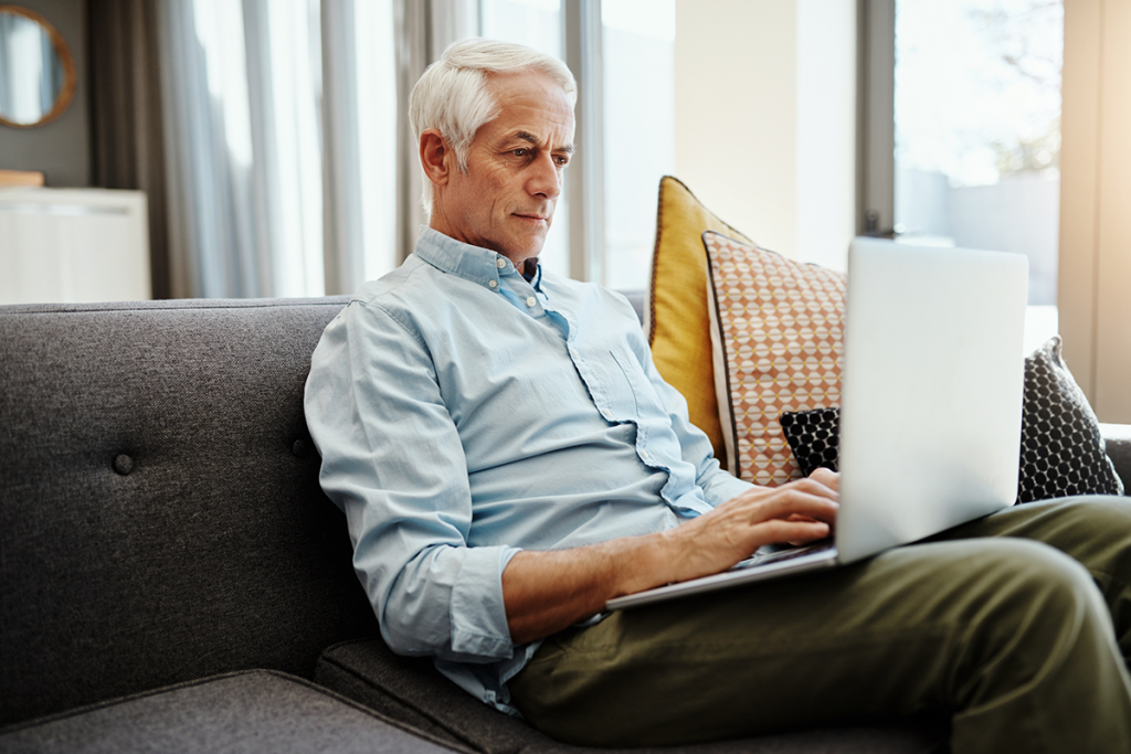 An older man uses telemedicine from his laptop