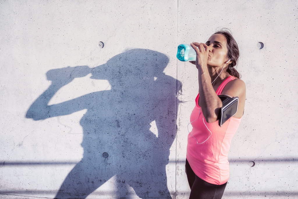 A woman takes a break from running to have some water in front of a concrete wall