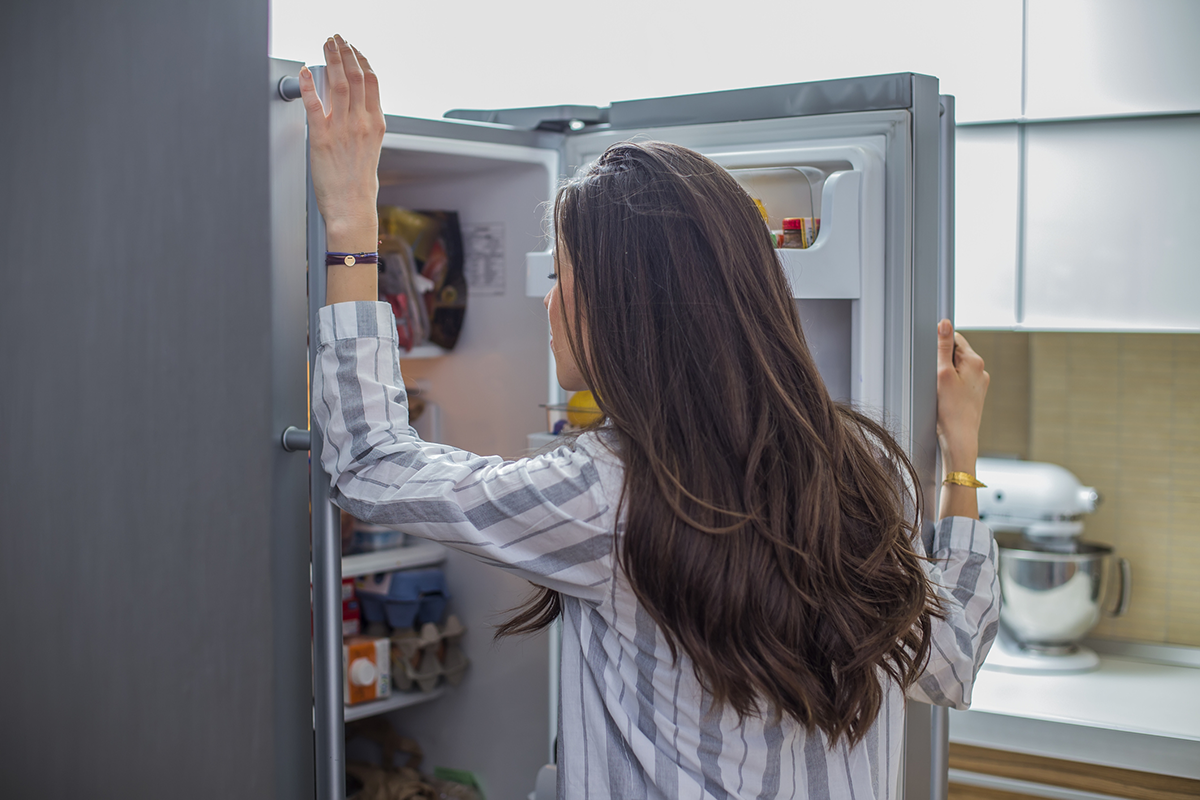 A woman looks into a refrigerator