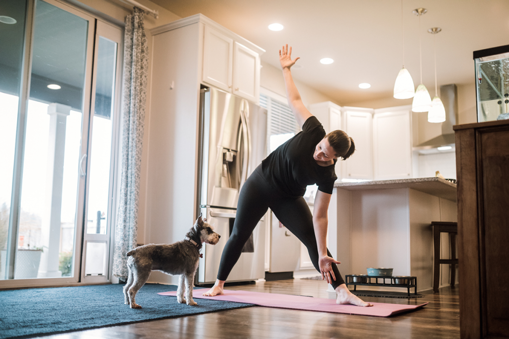 A woman stretches in her home, as a dog watches