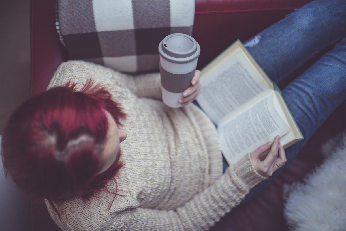 A young woman relaxes with a book and a cup of coffee.