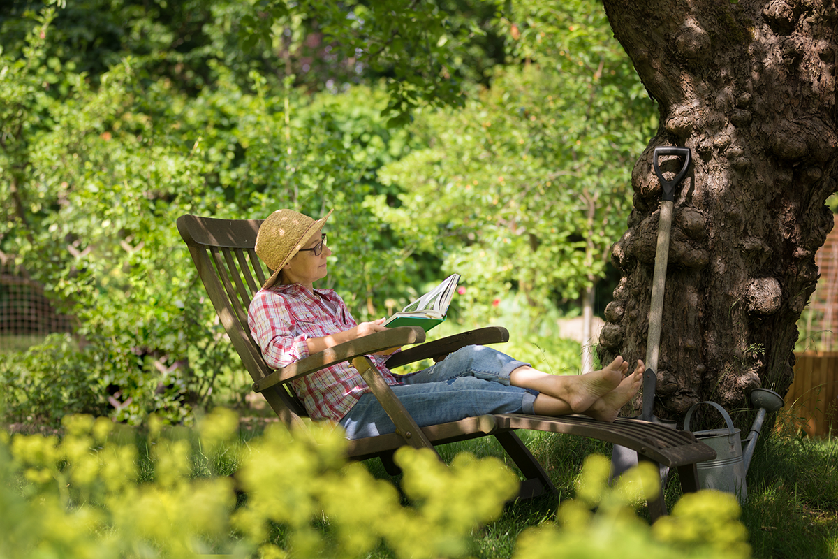 A woman reads in a shady garden