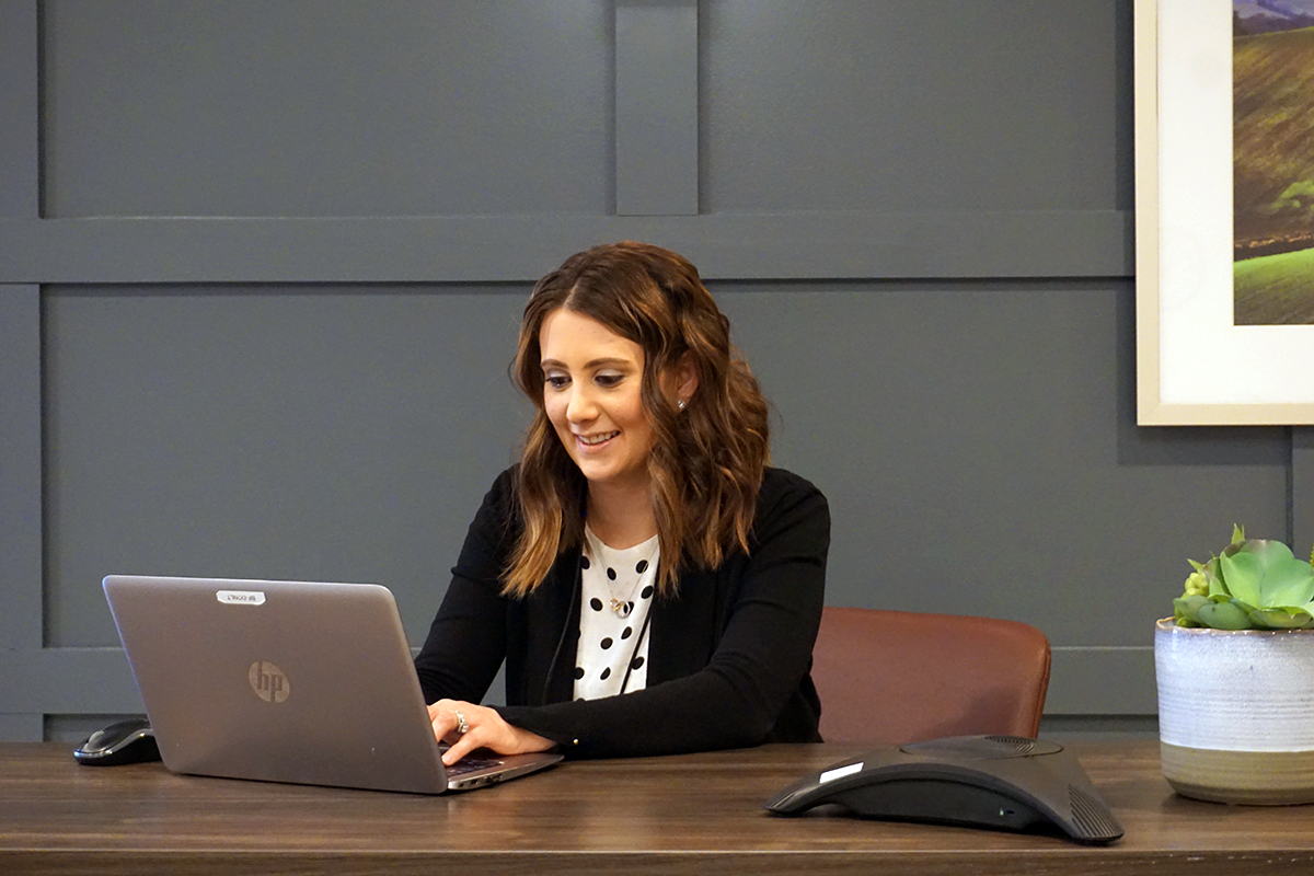 A photo of Laura Smith, using a laptop