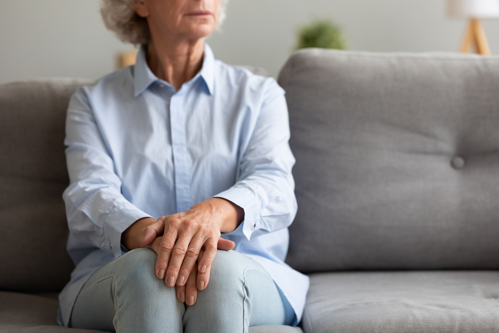An older woman sits on a sofa, hands on her legs, looking away with an air of sadness