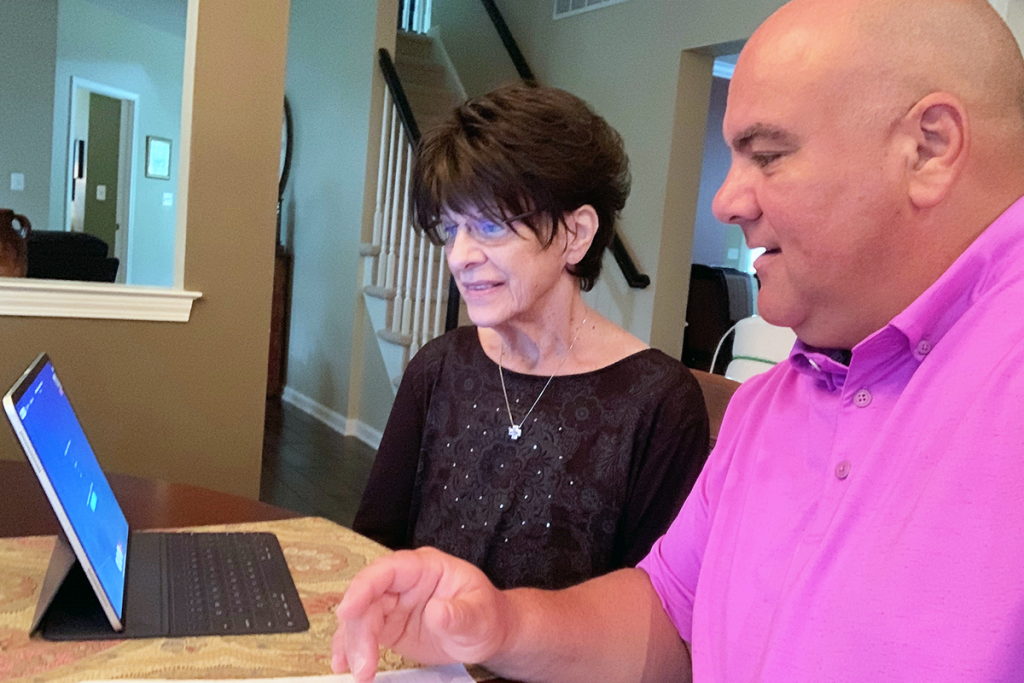 Peter Panageas helps his mother set up telemedicine on a tablet