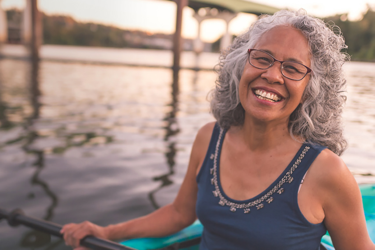 An older woman enjoys an evening of river kayaking