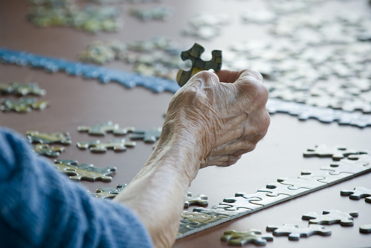 The hand of an older person placing a jigsaw puzzle piece