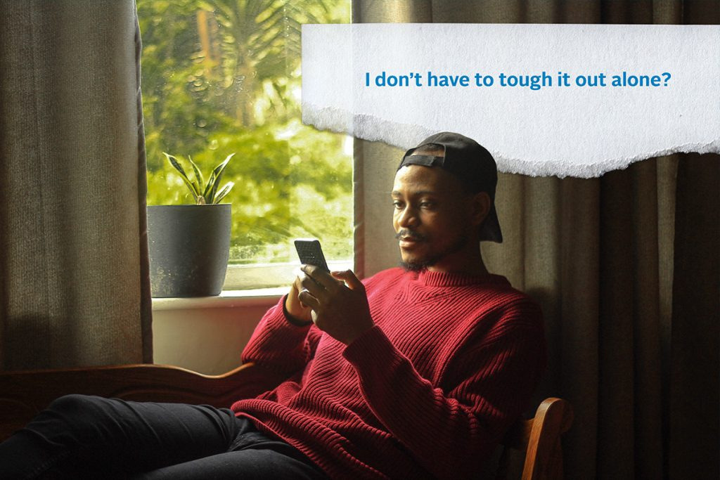 "A young man stares at his phone, a slightly sad expression on his face. Above his head, the words ""I don't have to tough it our alone?"""