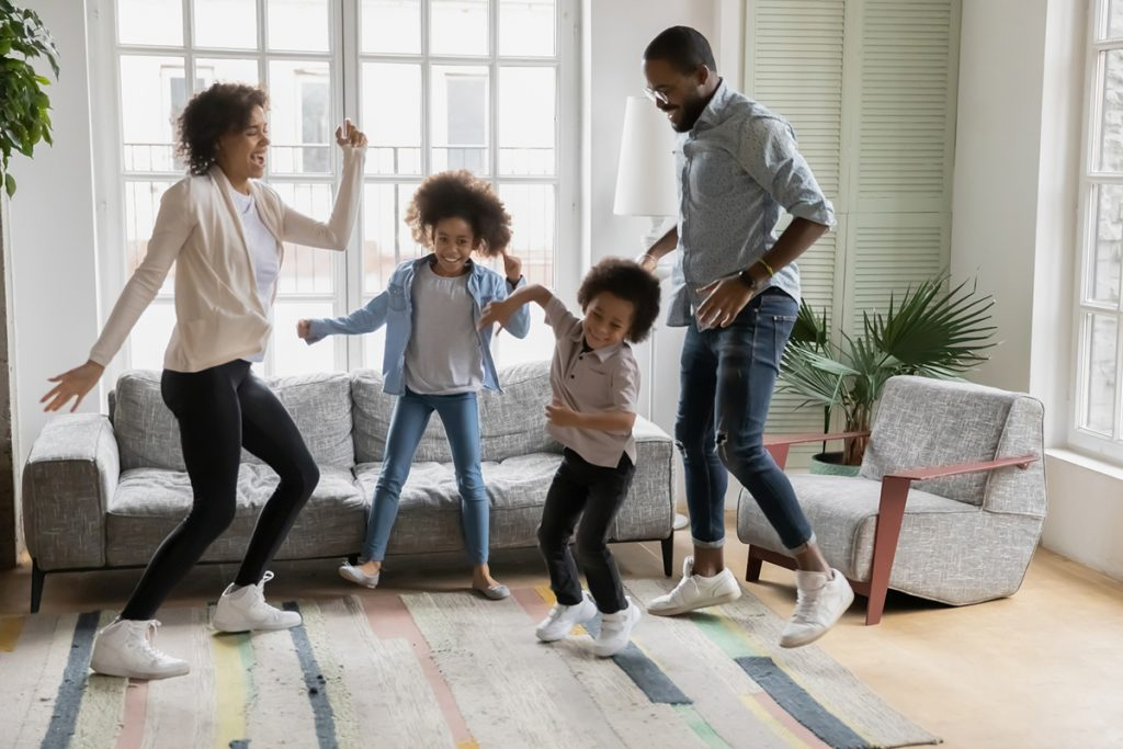 A family dances in their living room