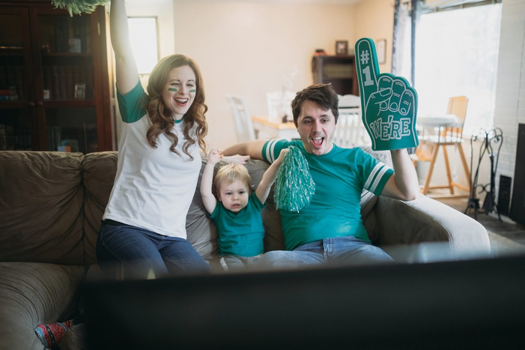 A happy family with a young child have fun goofing off while watching a sports game on the television. They wear their team color and celebrate a win!