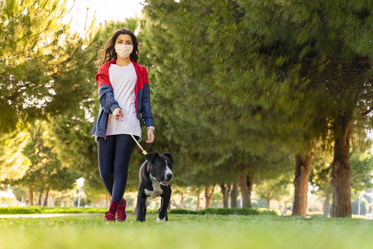 Woman wearing a protective mask is walking alone with a dog outdoors