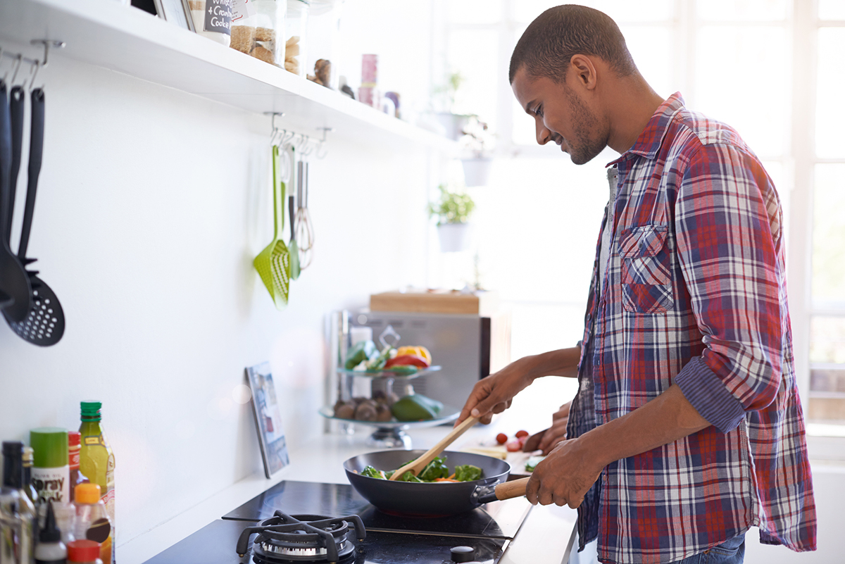 Young man cooking over a stove in his kitchen