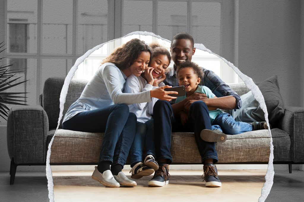A photo illustration of a family on a couch, smiling while talking with someone via video chat