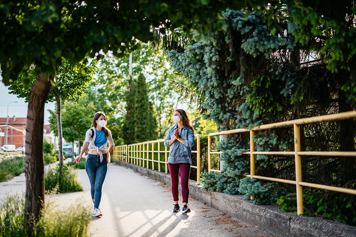 Two friends holding social distance during walk