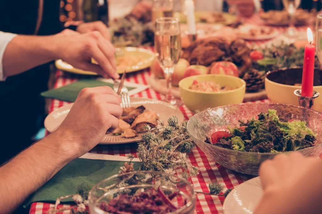 Hands cutting food on a plate during a holiday dinner.