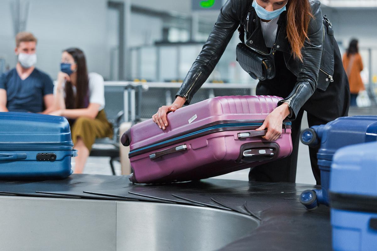 Airplane traveler wearing face mask receiving luggage from conveyor belt
