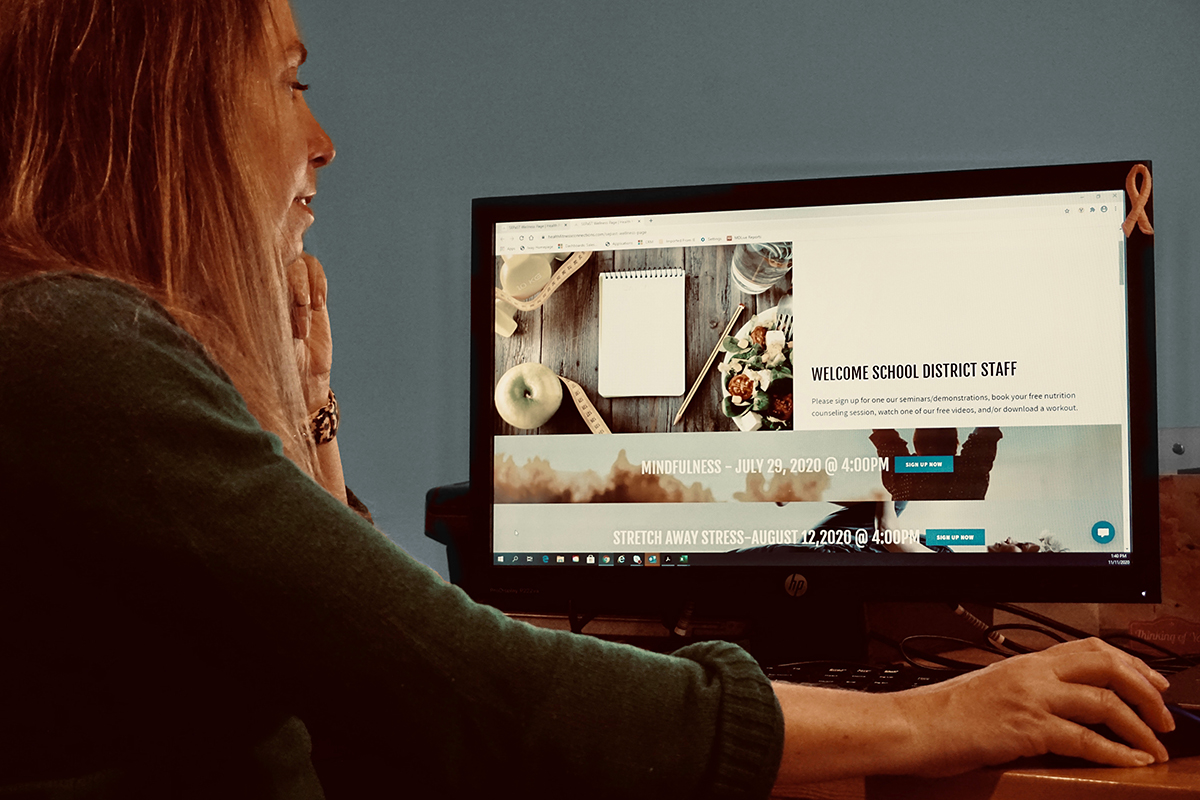 A woman looks at a virtual worksite well-being program on her computer.