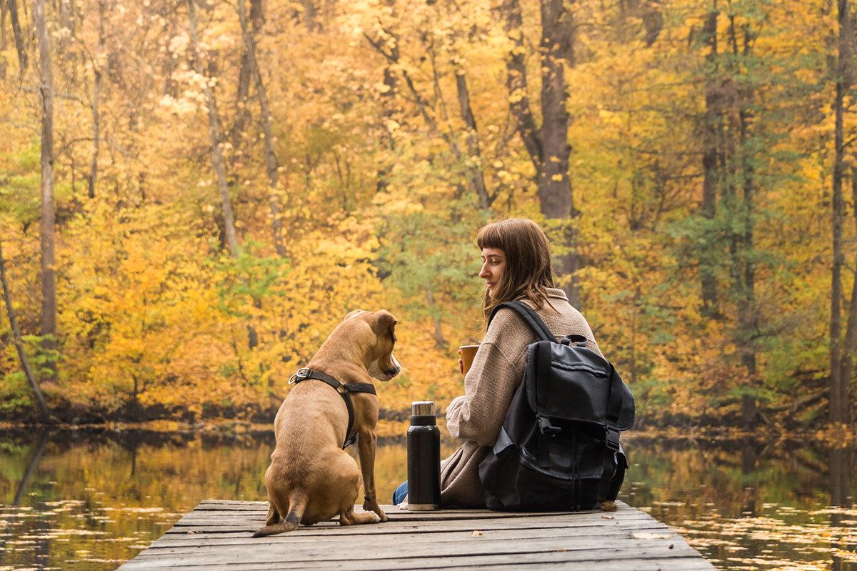 Girl hiker rests at riverbank with her pet dog and drinks coffee from thermos