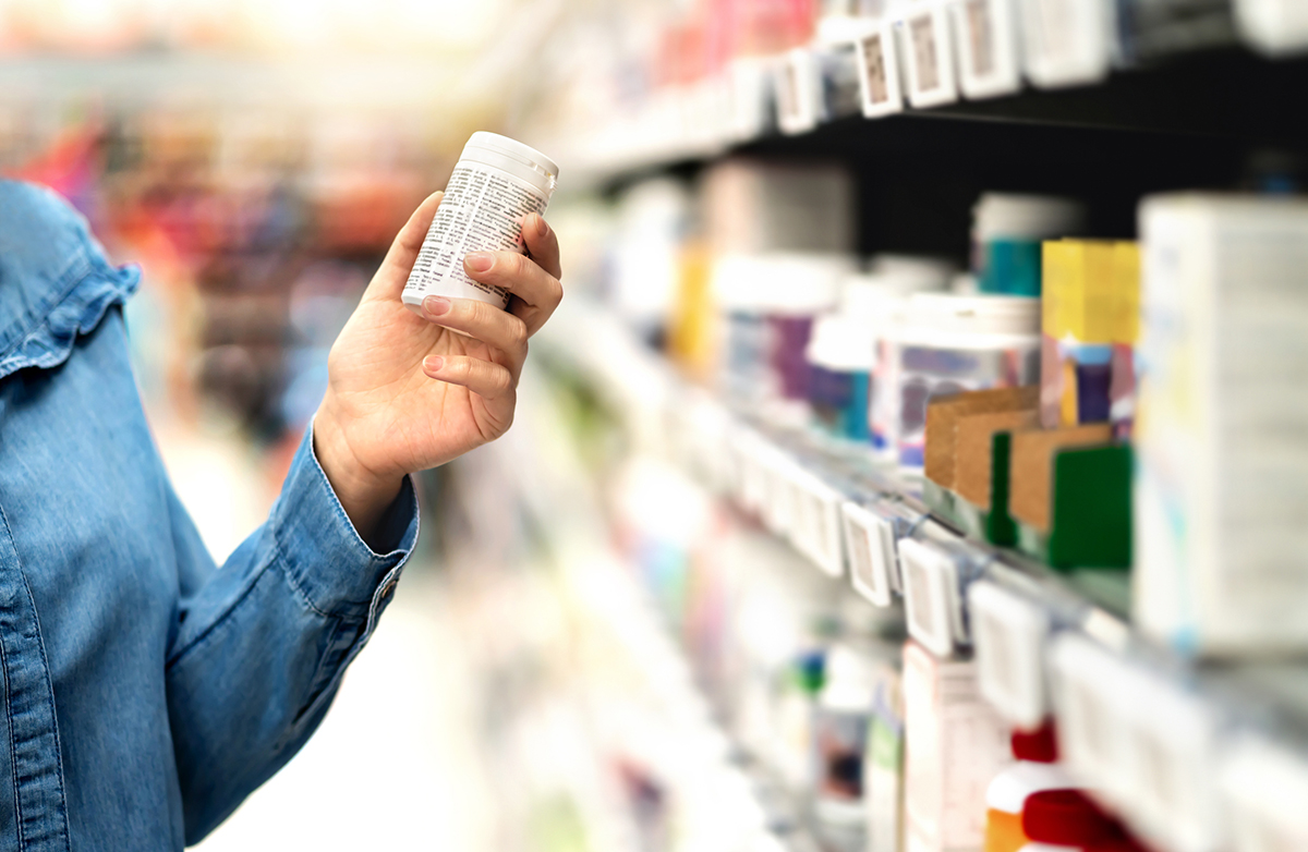 Customer in pharmacy holding medicine bottle. Woman reading the label text about medical information or side effects in drug store. Patient shopping pills for migraine or flu.