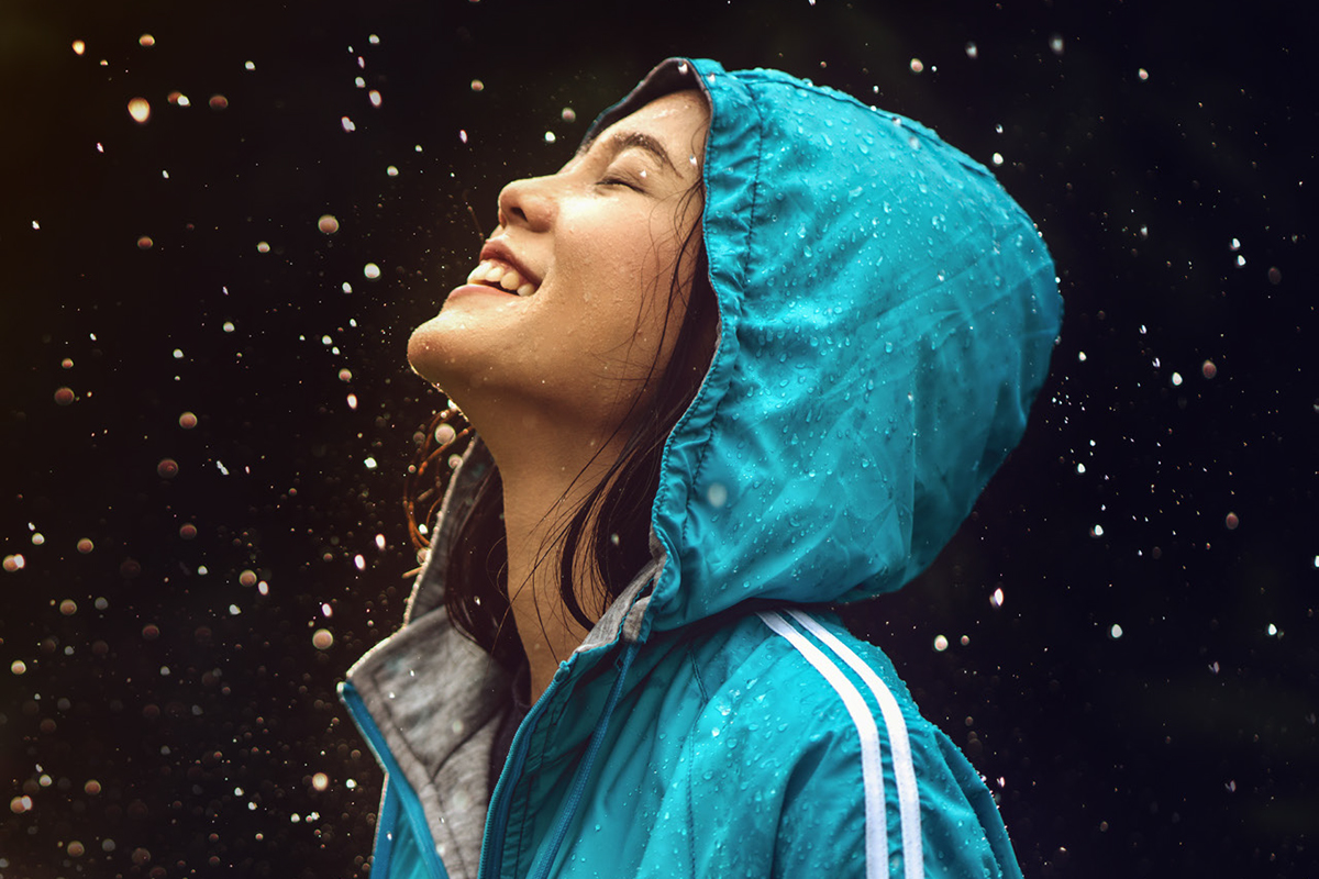 Woman wearing a raincoat outdoors. She is happy.