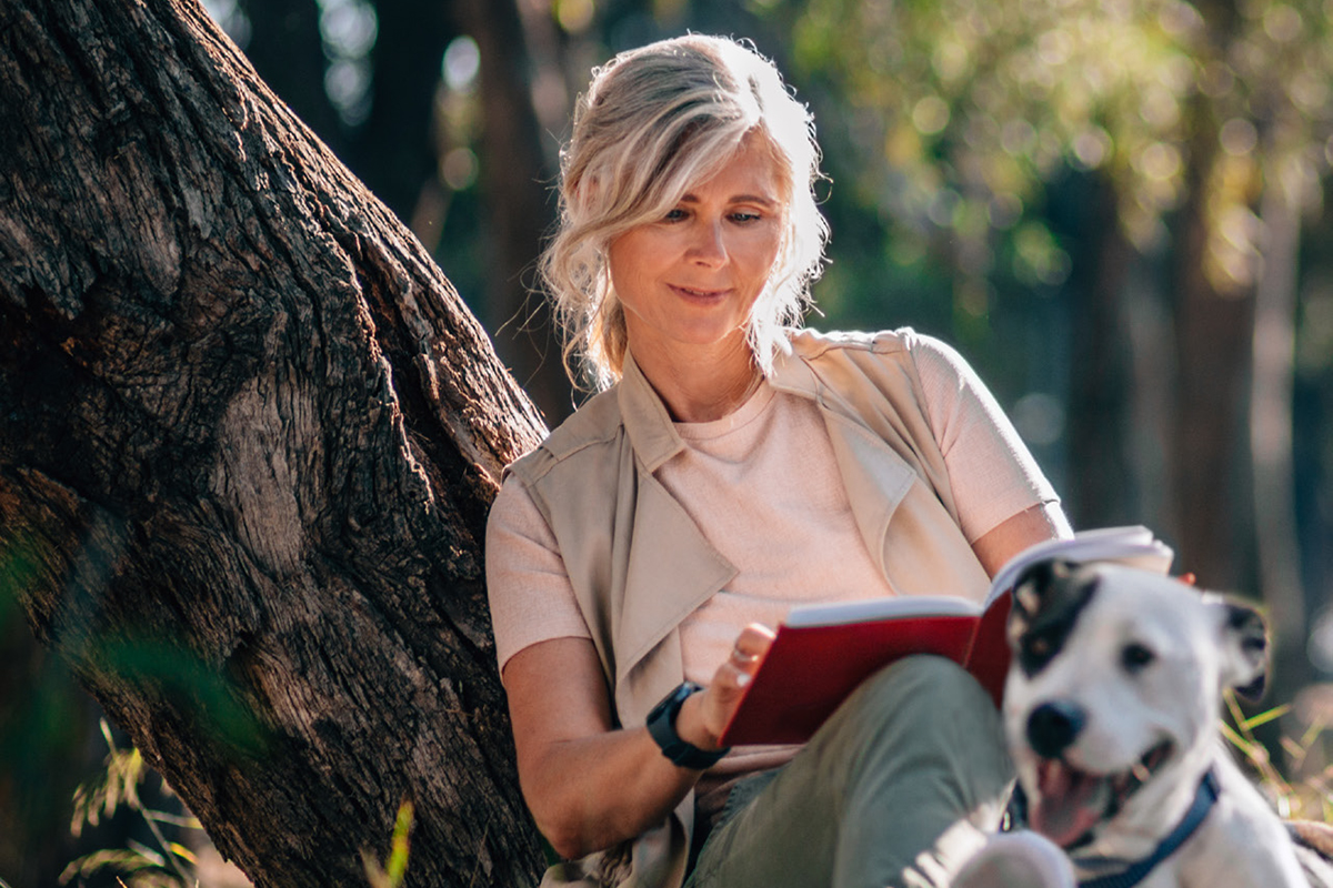 Senior woman relaxing in nature with book and pet dog