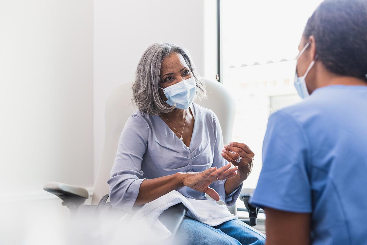 Senior woman talks with female healthcare professional