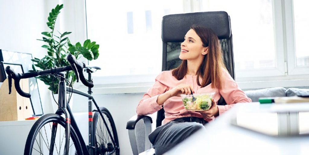 a brunette woman sits in an office chair eating a salad at her desk