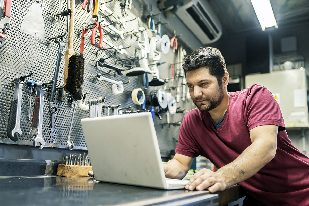 Photo of male Bicycle Mechanic with white laptop leaning on table in his workshop.