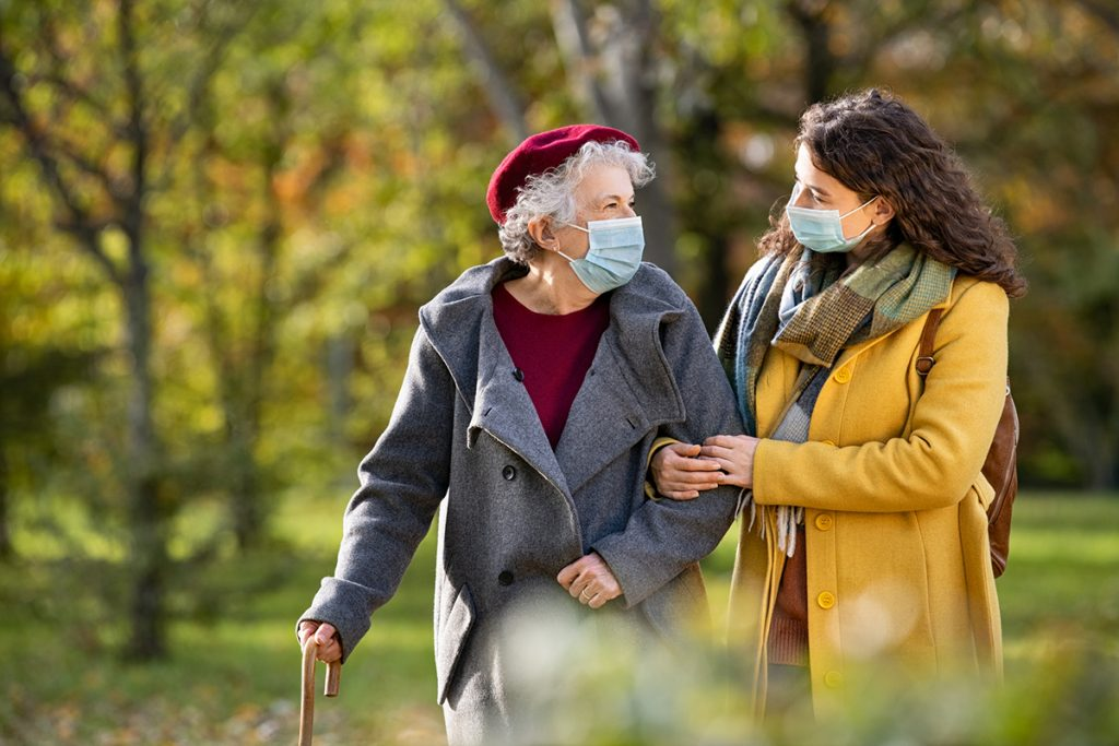 Senior woman with girl wearing face mask at park