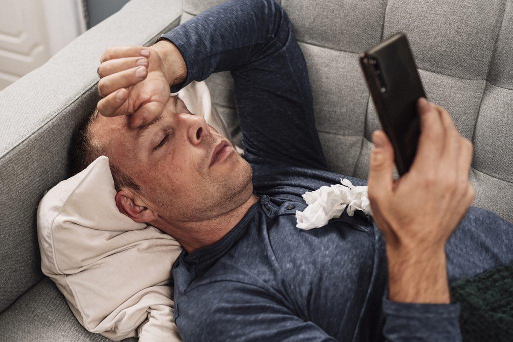 Sick man using telemedicine on his phone