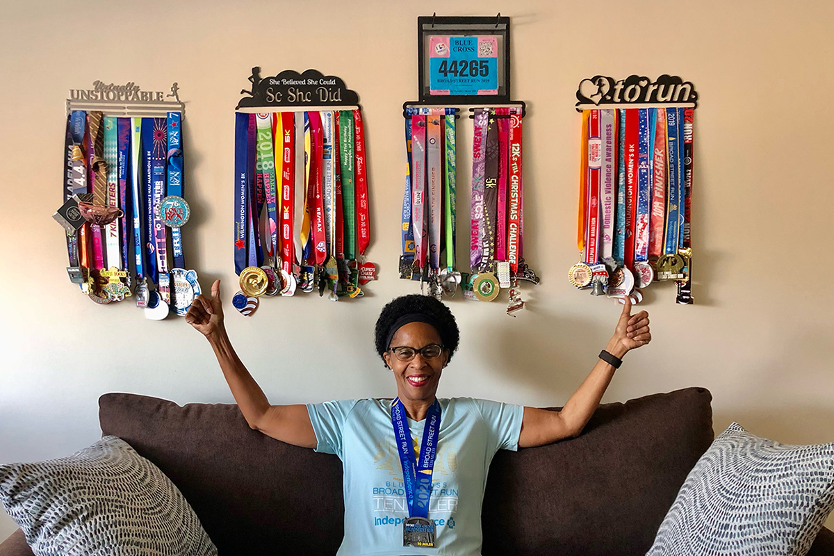 Nurse Health Coach Tina Odim flashes a big smile and two thumbs up in front of her collection of race finisher medals.