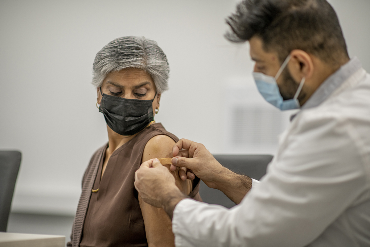 Doctor puts a band aid on an older woman's arm after vaccination