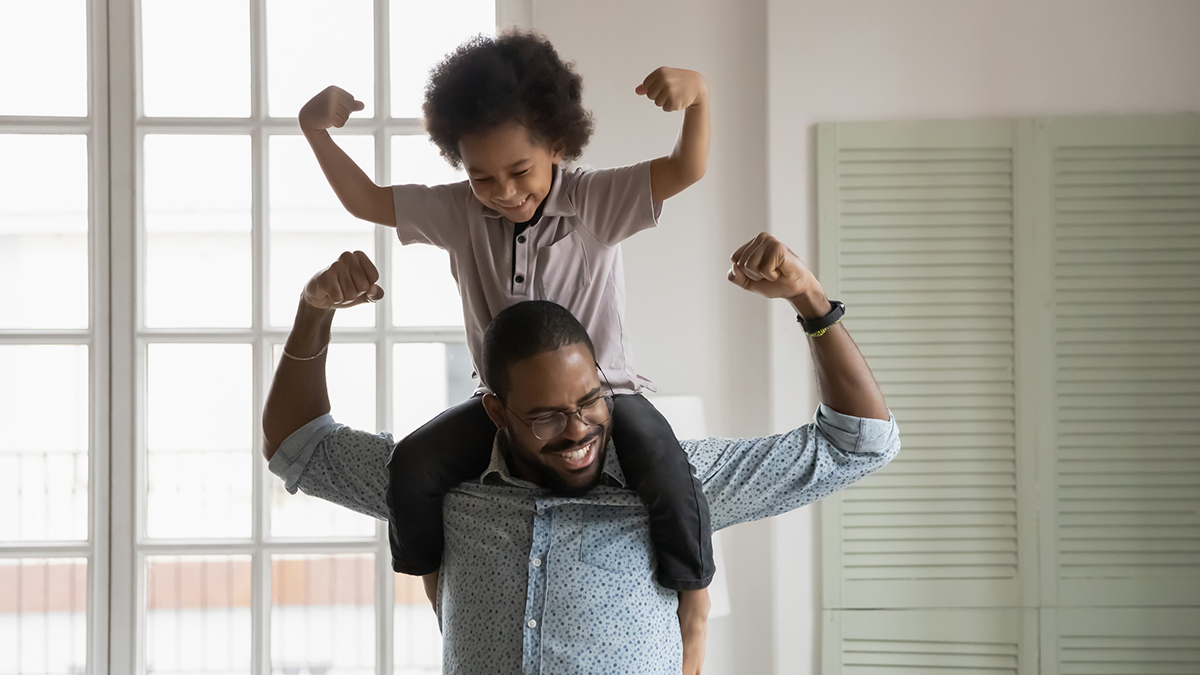 A father holds his son atop his shoulders